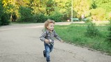 Curly little boy running in the park. He is very cute and funny.