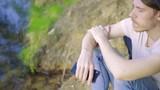 Парень на берегу озера снимает видео на смартфон в драных джинсах в кепке