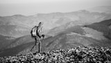 Male sportsman backpaker walking on the rocky mountain ridge with beautiful mountains on background. Man is wearing jacket and has trekking sticks and backpack on. Sunny day. black and white
