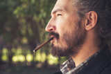 Man smoking cigar, outdoor profile portrait