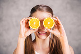 Girl covering eyes with oranges