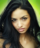 Beautiful exotic young woman in wild natural setting with slight rain falling on hair. Image cross processed.