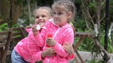 Girl blowing bubbles, suddenly her arms around the other girl, and together they continued to blow bubbles