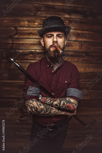 Attractive bearded male with tattooes on arms. Poster