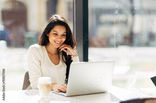Brunette using laptop in cafe Poster