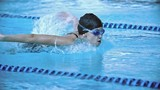 Side view of sportswoman in cap and goggles swimming butterfly stroke in pool in slow motion