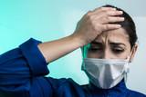 ritratto di medico con camice blu e mascherina bianca che si tiene la testa in segno di disperazione - sfondo verde