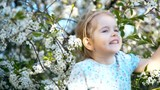 little girl smelling the cherry flowers and smiling