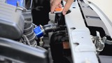 Hand of man using blue micro fiber fabric to clean car and open the radiator cap