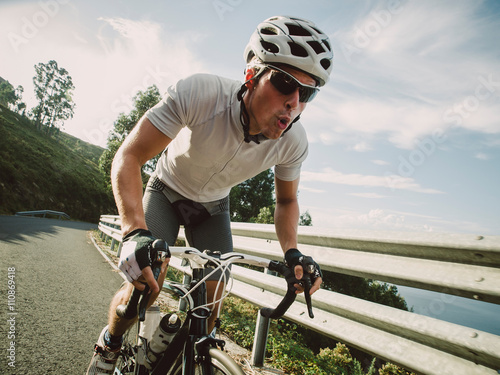 Cyclist in maximum effort pedaling outdoors