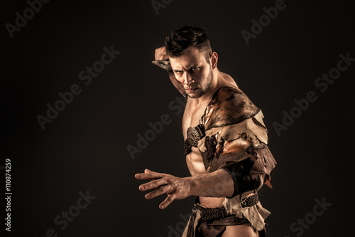 Poster Severe barbarian in leather costume with sword