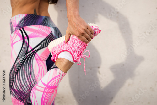 Fototapeta Urban fashion running running sportswear. Female athlete stretching legs after exercising. Healthy lifestyle and sport concept.