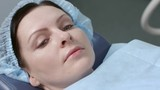 Female patient in conscious lies on operating table