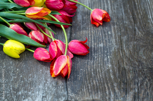 Staande foto Roses colorful tulips on wooden surface