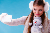 Woman with little snowman taking selfie photo.