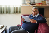 Mature man reading e-book when sitting on sofa