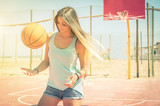 Sporty caucasian girl playing basketball