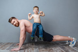 Smiling father doing push-ups with son sitting on back
