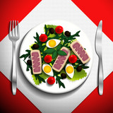 Nicoise salad with tuna steak, basil, olives, tuna, egg, tomatoes and arugula on white plate.