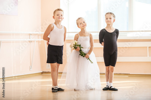 At ballet dancing class: young boys and a girl with flowers posing gracefully  © Andrey Bandurenko