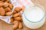 Almond milk in glass with almonds seeds.