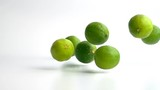limes falling in slow motion against white drop