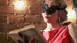 Young pretty woman in a black mask sitting near the brick wall reading a book. Fashion 18th century. RAW video record.
