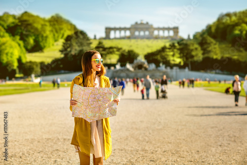 Foto op Canvas Wenen Young female tourist traveling with paper map in Schoenbrunn palace with Gloriette building on the background