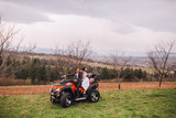 Fototapety Happy beautiful couple driving four-wheelers ATV and looking at each other.