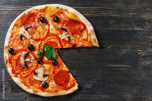 Foto op Canvas Pizzeria Top view of Italian rustic PIZZA mushrooms, basil, tomato, olives and cheese. Cut off a piece and pushed. Dark wooden table background. Look as Prosciutto, Capricciosa, Funghi, Cotto PIZZA.