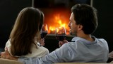 Happy couple clinking red wine glasses near fireplace