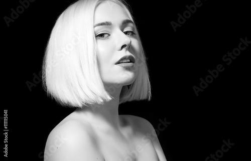 Blonde with shiny short hair and bare shoulders on a black backg © deniskomarov