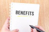 Benefits word on white ring binder notebook with hand holding pe