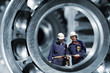 industrial engineering parts with two workers inside giant ball-bearing