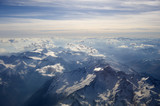 High altitude view of sunset over the mountains. Rays of light shine through the hazy atmosphere.