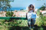 tourist child girl with map traveling on summer vacations in Piran, Slovenia