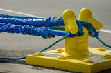 Heavy blue ropes of an ocean-going ship wrap around a yellow mooring bollard on a city pier in the harbor. - 111203499