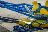 Heavy blue ropes of an ocean-going passenger ship wrap around a yellow mooring bollard on a city pier in the harbor. - 111203630