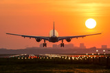 Fototapety Passenger plane is landing during a wonderful sunrise.