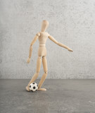 Concept of football or soccer. Wooden puppet playing with ball in conceptual studio image. Idea of having fun with sport.