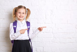 Fototapety Cute smiling schoolgirl in uniform standing on light  background and showing  thumbs to the side. Copy space