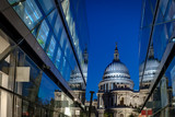 St Paul's cathedral seen from a narrow alley enclosed by glass buildings on a clear night in summer