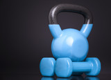 A kettlebell and two dumbbells on black background