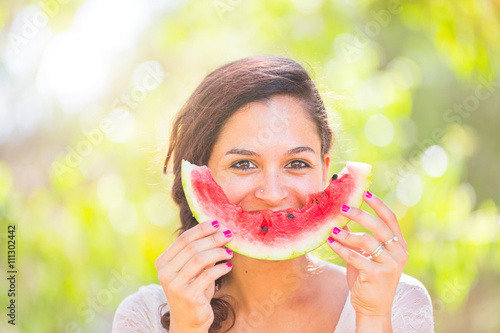 Plagát Beautiful young woman at park eating a slice of watermelon