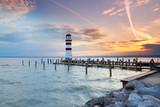 Leuchtturm am Ende eines Holzsteges, See zum Sonnenuntergang