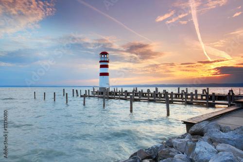 Fototapeta Leuchtturm am Ende eines Holzsteges, See zum Sonnenuntergang