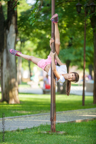 Cute girl having fun outdoor using a street lamp as a gymnastic pole © Andrey Bandurenko