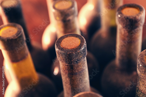 Stacks of dusty wine bottles on wooden background, upside view. Close up © Africa Studio