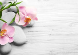 Fototapety Spa stones, bamboo stack and orchid flowers on wooden background