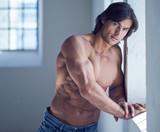 Portrait of suntanned muscular guy in denim jeans.